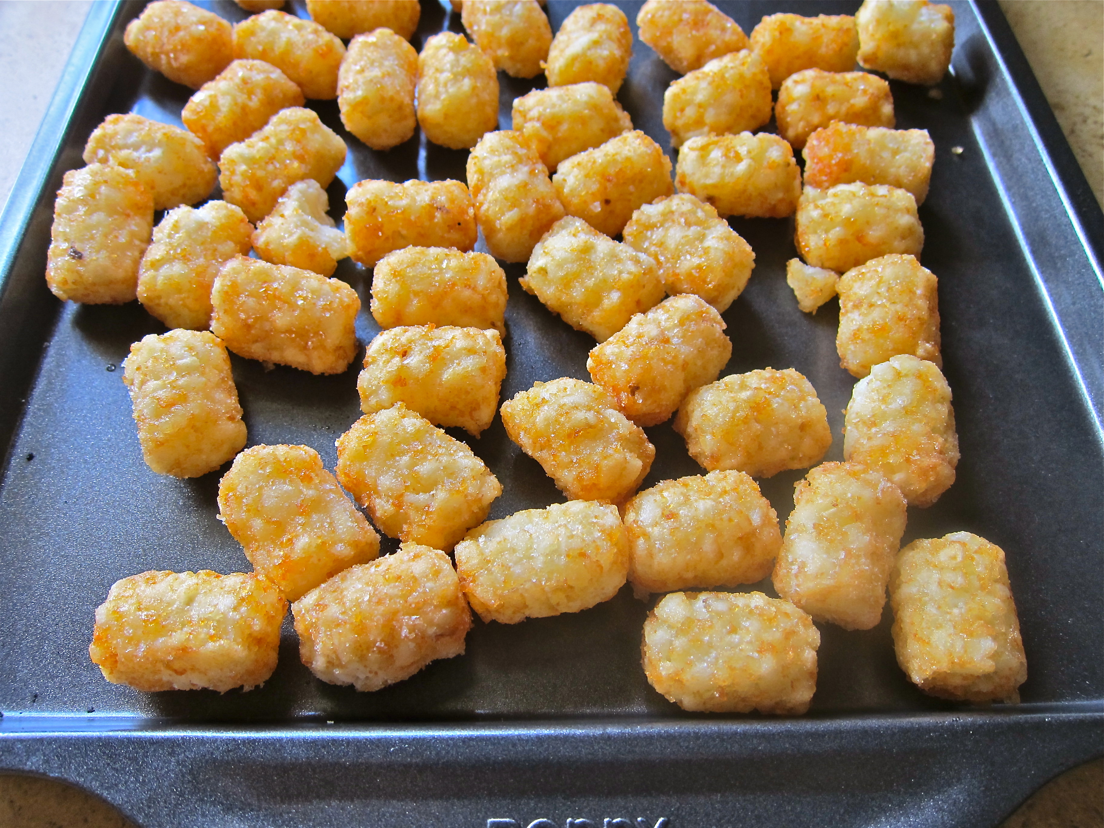 Throw half a bag of frozen hash browns (tater tots) on a baking sheet ...